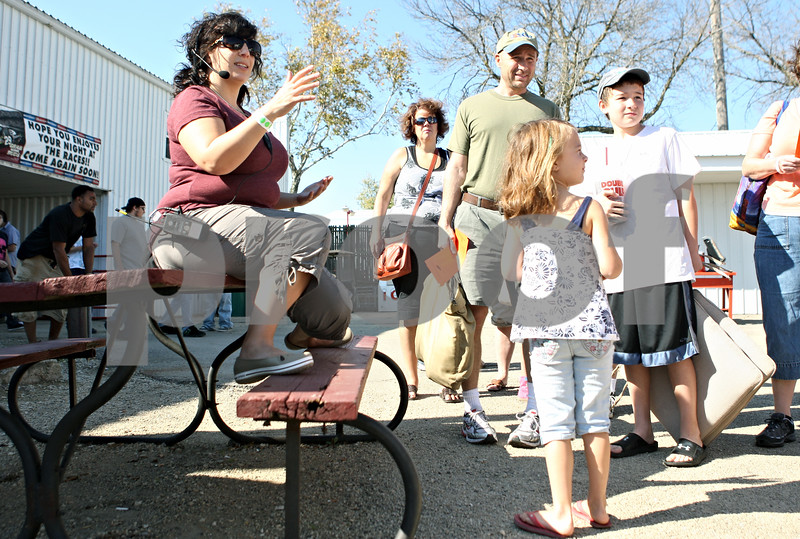 Rob Winner – rwinner@shawmedia.com<br /> <br /> Jess Gisin (left) greets a group of hopeful movie extras inside the Sycamore Speedway as filming for a movie starring Quaid and Zac Efron continues in Maple Park on Saturday, Oct. 8, 2011.