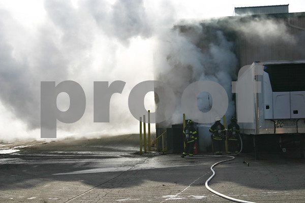 ANDREW MITCHELL — amitchell@shawmedia.com<br /> Firefighters extinguish a burning electrical transformer Monday on the northeast side of the Tegrant Building in DeKalb. Officials said there was an explosion in the transformer, which also set fire to a parked semi-trailer and the inside of the building.