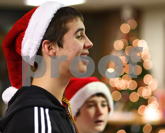 Kyle Bursaw – kbursaw@shawmedia.com<br /> <br /> Andrew Stratton, 17, and Aaron Pope, 11 (background) sing Christmas carols with the God Squad youth group at Oak Crest Retirement Center in DeKalb, Ill. on Wednesday, Dec. 14, 2011.