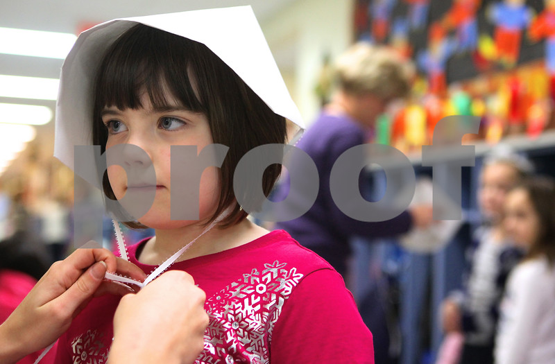 Kyle Bursaw – kbursaw@shawmedia.com<br /> <br /> Danielle Clements ties a paper bonnet on Bella Rieff before the kindergarten's Thanksgiving feast at Davenport Elementary School in Genoa, Ill. on Tuesday, Nov. 22, 2011.