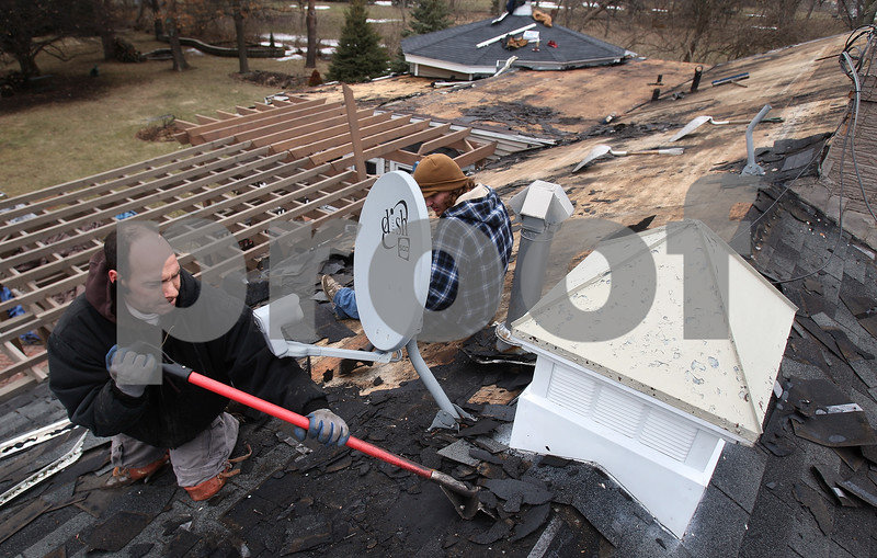 Kyle Bursaw – kbursaw@daily-chronicle.com<br /> <br /> Andrew Kellogg, owner of DeKalb Roofing, tears off the old roofing prior to installing new roofing at a residence in Cortland, Ill. on Thursday, March 10, 2011.