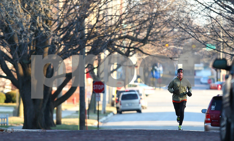 Kyle Bursaw – kbursaw@shawmedia.com<br /> <br /> Cohen Barnes runs south on Third Street during his morning run on Friday, Dec. 23, 2011. Barnes is just a few days away from completing his 2011 New Year's resolution of running at least three miles each day. His 2012 resolution is to complete a marathon in under four hours.
