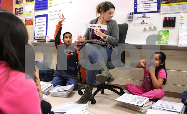 Kyle Bursaw – kbursaw@shawmedia.com<br /> <br /> Carlos Cruz raises his hand to make a comment as Cortland Elementary teacher Alex Fausett listens to a comment from Julia Alvarez (right) as the bilingual fifth grade classroom discusses, in Spanish, people who they think fit the definition of altruism in Cortland, Ill. on Thursday, Nov. 17, 2011.