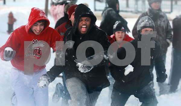 Kyle Bursaw – kbursaw@daily-chronicle.com<br /> <br /> Northern Illinois students, from left, Fernando Montoia, Aaron Briggs and Guide Sobecki, charge their opponents during a snowball fight on campus on Wednesday, Feb. 2, 2011.