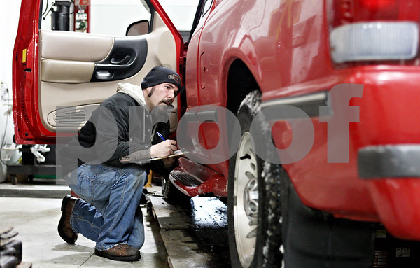 Rob Winner – rwinner@daily-chronicle.com<br /> <br /> Sean Sheridan, a mechanic at Bockman's Auto Care in Sycamore, takes notes before servicing a vehicle on Monday afternoon.
