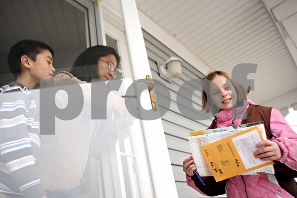 Rob Winner – rwinner@daily-chronicle.com<br /> <br /> Sycamore residents Nathaniel Bisco (left), 9, and his mother Gladys Bisco purchase Girl Scout cookies from Katie Steponaitis, 9, of Brownie Troop 355 on Monday afternoon.