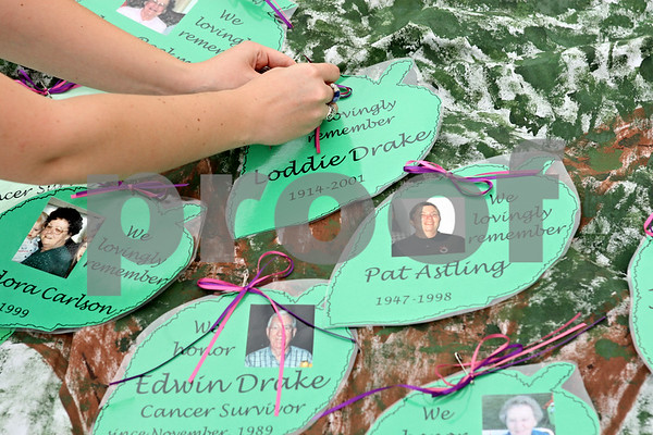 Rob Winner – rwinner@daily-chronicle.com<br /> <br /> Before the start of Relay for Life of DeKalb County on Friday evening in Sycamore, Eva Weil puts together a memory tree with the names and photographs of survivors and those who have passed because of cancer.