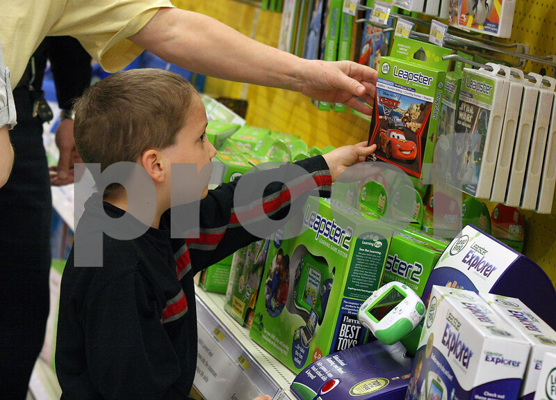Wendy Kemp - For The Daily Chronicle<br /> Justin Miller, 7, picks out a toy during the Shop with a Cop event at Target on Sunday.<br /> DeKalb 12/11/11