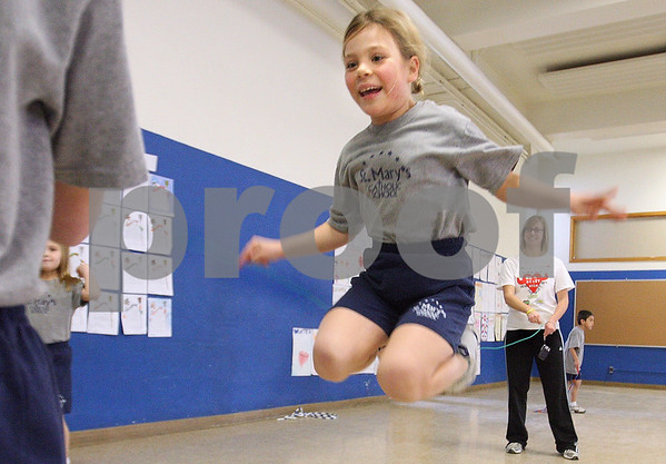 Kyle Bursaw – kbursaw@daily-chronicle.com<br /> <br /> Katelyn Kolkebeck hops over a long jump rope as fellow second-grader Noelle Simone (left) and teacher Cris Zakosek spin the rope for Kolkebeck. The physical education classes at St. Mary School and other local schools are participating in Jump Rope for Heart.<br /> <br /> Wednesday, Feb. 9, 2011.