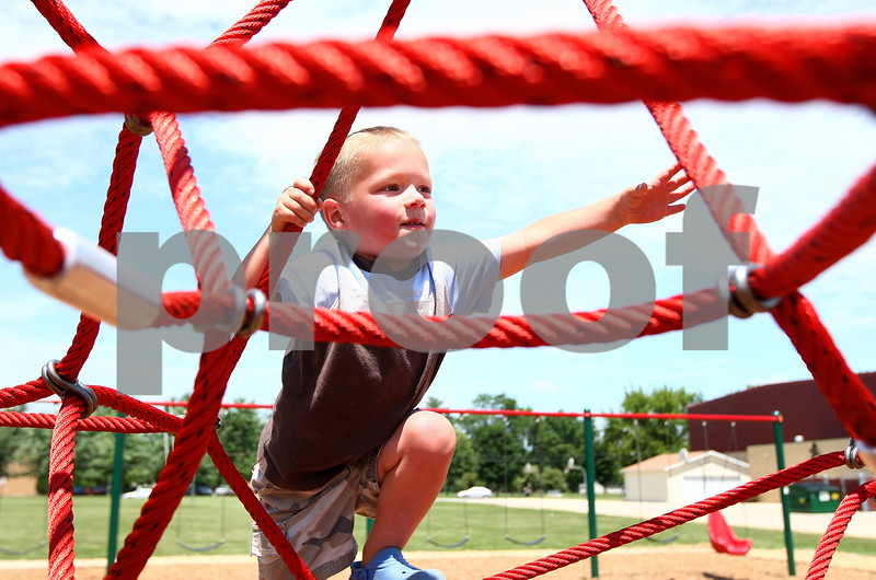 Kyle Bursaw – kbursaw@daily-chronicle.com<br /> <br /> Lincoln Fifer, 3, climbs the ropes at the new playground at Founders Elementary on Thursday, July 14, 2011.