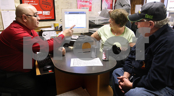 Kyle Bursaw – kbursaw@daily-chronicle.com<br /> <br /> John Saponari, left, points to the potential tax refund amount he came up with for Myrna and Bjarne 'Bob' Christensen at Jackson Hewitt Tax Service in DeKalb, Ill. on Thursday, Feb. 17, 2011.