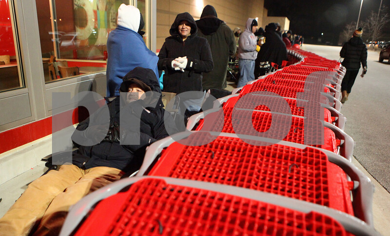 Kyle Bursaw – kbursaw@shawmedia.com<br /> <br /> J.R. Jensen, of DeKalb, relaxes just inside a barricade of shopping carts, where he was also in position to secure one of the discounted 46-inch televisions on sale at Target late on Thursday, Nov. 24, 2011. Jensen started waiting in line around 4:30 p.m. on Thursday.