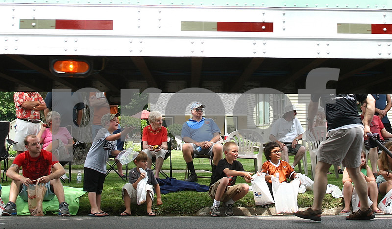 Kyle Bursaw – kbursaw@daily-chronicle.com<br /> <br /> Attendees of the Genoa Days parade watch and collect candy as a truck passes by them on Saturday, June 18, 2011.