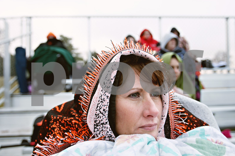 Rob Winner – rwinner@daily-chronicle.com<br /> <br /> Covered in blankets, DeKalb resident Angie Kennedy watches as her daughter, Kaylin Kennedy, pitches for the Barbs during the third inning in DeKalb on Wednesday afternoon.
