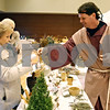 "Rob Winner – rwinner@shawmedia.com<br /> <br /> Earline Unger (left), of Ashton, receives some lavender for one coin from vendor Ron Ekena during a ""Night in Bethlehem Market Place"" at St. John Lutheran Church in Sycamore on Saturday, Dec. 10, 2011."