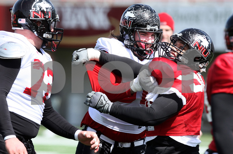 Kyle Bursaw – kbursaw@daily-chronicle.com<br /> <br /> Left tackle Trevor Olson immobilizes Alan Baxter (right) at the line during practice at Huskie Stadium on Saturday, March 26, 2011.