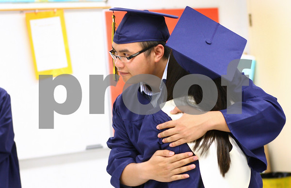 Kyle Bursaw – kbursaw@daily-chronicle.com<br /> <br /> Quan Nguyen hugs fellow Hiawatha senior Diana Ascencio in a classroom before Hiawatha's graduation ceremony on Friday, May 27, 2011.