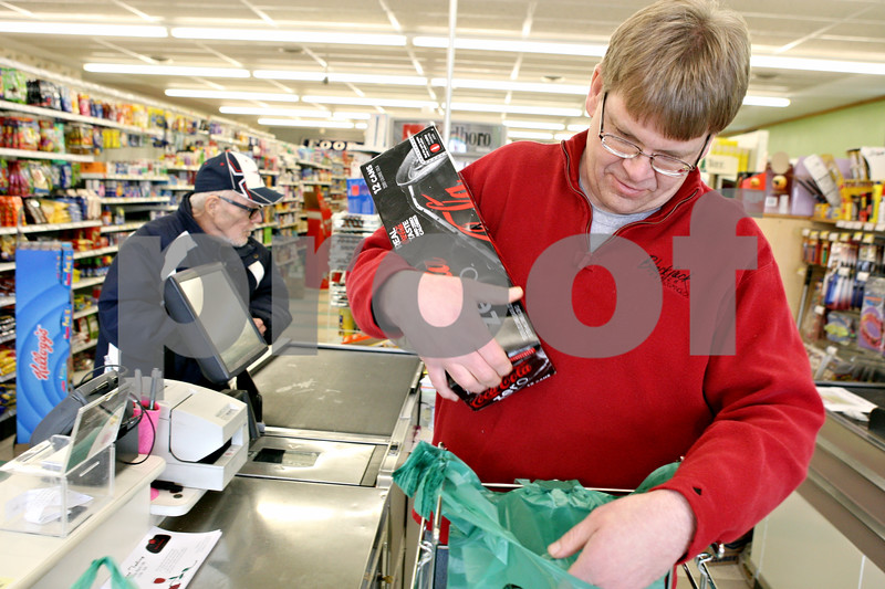 Rob Winner – rwinner@daily-chronicle.com<br /> <br /> Owner Tom Wisted (right) of Wisted's Country Market in Shabbona bags groceries for Marty Thorsen on Tuesday afternoon.