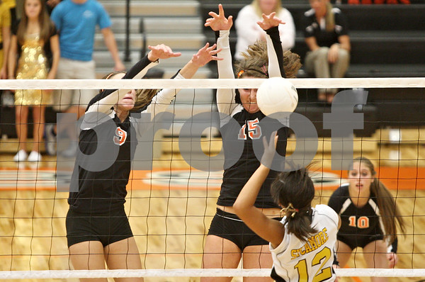 Rob Winner – rwinner@shawmedia.com<br /> <br /> Sycamore's Mattie Hayes (12) has her kill attempt blocked by DeKalb's Emily Bemis (15) during the first game in DeKalb on Wednesday, Oct. 5, 2011. DeKalb defeated Sycamore, 28-26 and 25-19.