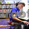 Kyle Bursaw – kbursaw@shawmedia.com<br /> <br /> Maria Holloway-Racine pets Tucker, a certified therapy dog, while reading a book to him in the DeKalb Public Library on Friday, Aug. 19, 2011.