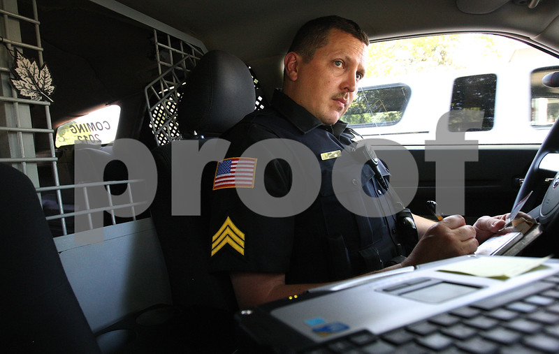 Kyle Bursaw – kbursaw@daily-chronicle.com<br /> <br /> Sergeant Robert Smith glances at his computer while on a traffic stop where he issued a warning to the driver for not wearing a seat belt in Genoa, Ill. on Tuesday, June 28, 2011. Behind Smith is the kennel for a K-9 officer. The Genoa police department is raising money for a new K-9 officer and still has a fully equipped vehicle from when they last had one.