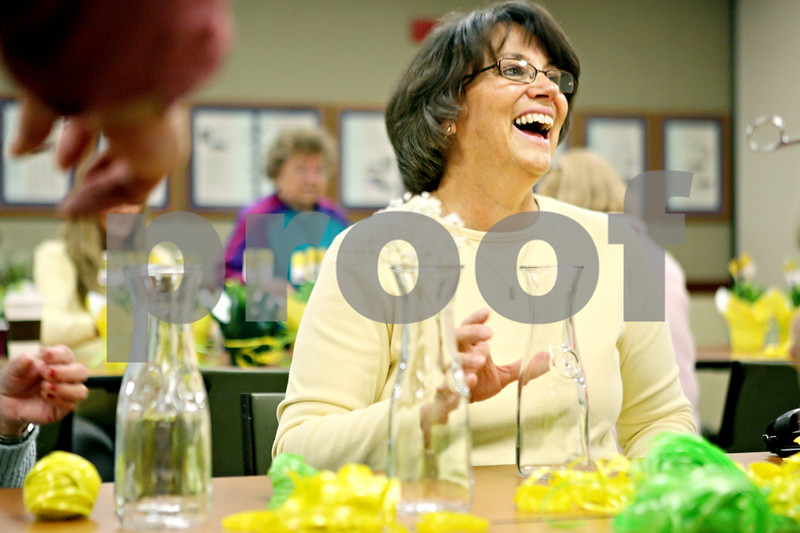 """Rob Winner – rwinner@daily-chronicle.com<br /> <br /> Jodi Tyrrell, of Sycamore, shares a laugh with fellow volunteers while making flower bunches during the American Cancer Society Daffodil Days program at the Kishwaukee Community Hospital in DeKalb on Monday morning. Tyrrell, who is a cancer survivor said, """"It's a great group of people to work with. It's just part of the whole healing process."""""""