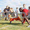 Rob Winner – rwinner@daily-chronicle.com<br /> <br /> Nathan Nailor, 10, leaps toward a tackle dummy as Northern Illinois University cornerbacks coach Richard McNutt encourages him during the DeKalb Bengals Football Camp in DeKalb on Monday evening.