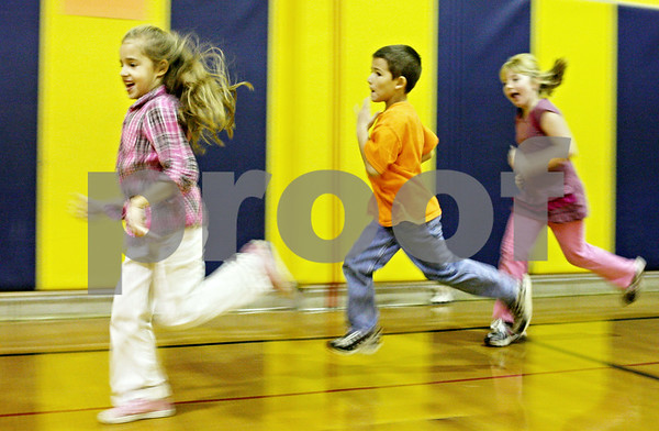 Rob Winner – rwinner@shawmedia.com<br /> <br /> (From left to right) Hiawatha Elementary students Alissa Malugen, 6, Kurtis Ruegsegger, 6, and Alivia Cooper, 6, run around the gymnasium while circuit training on Thursday, Nov. 3, 2011. The Kirkland school has for the second time in three years been named state champion in its division in the President's Council of Physical Fitness competition.