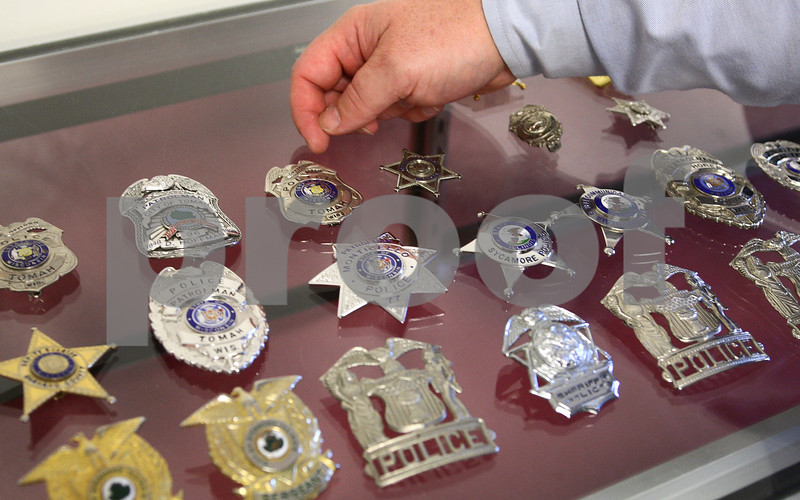 Kyle Bursaw – kbursaw@daily-chronicle.com<br /> <br /> Daniel Hoffman, a detective with the Sycamore Police Department, explains some of the different badges in his collection on Wednesday, June 29, 2011.