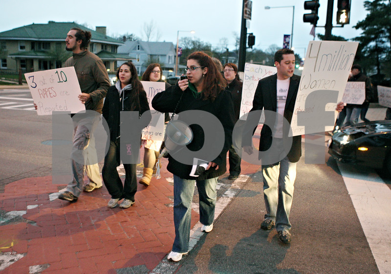 Rob Winner – rwinner@daily-chronicle.com<br /> <br /> Amanda Schrems, sexual assault coordinator for Safe Passage, leads a chant during Take Back the Night as participants cross First Street in downtown DeKalb on Thursday evening.