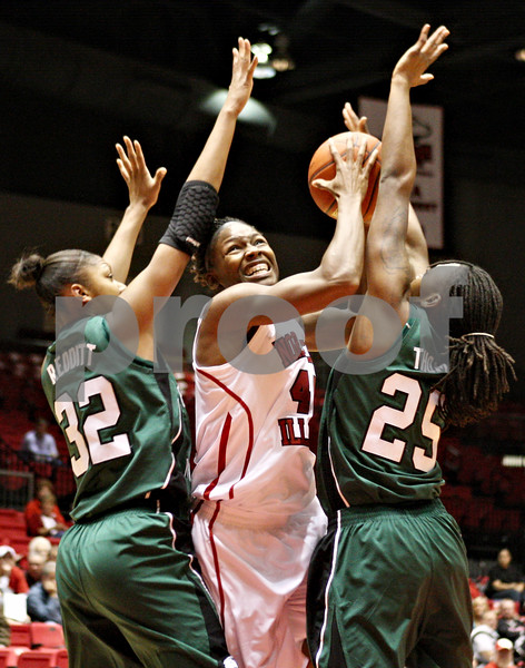 Rob Winner – rwinner@daily-chronicle.com<br /> <br /> Northern Illinois center Ebony Ellis looks to shoot while being pressured by two Eastern Michigan defenders, including forward Paige Redditt (32) and forward Kristin Thomas, during the first half of their game in DeKalb, Ill. on Wednesday, Jan. 5, 2011.