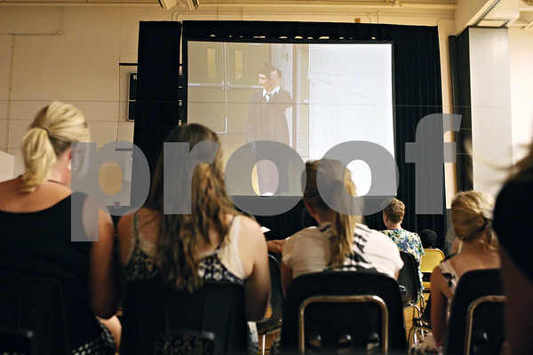 Rob Winner – rwinner@daily-chronicle.com<br /> <br /> From an auxiliary gymnasium with a projector screen, guests of  the Sandwich Community High School commencement ceremony watch as Dritan Zulbeari enters the main gymnasium on Sunday in Sandwich.