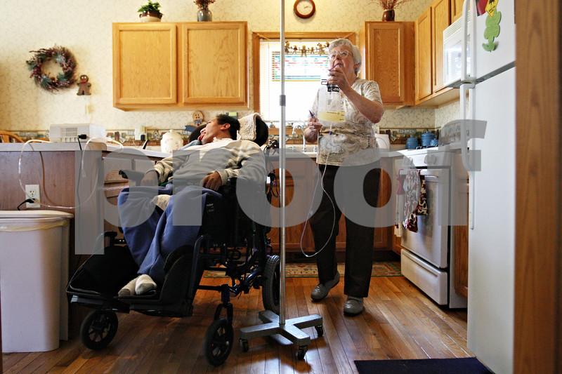Rob Winner – rwinner@daily-chronicle.com<br /> <br /> Eileen Bosshart, 78, prepares an antibiotic for John Shepherd, 44, in the kitchen at Bosshart's home in Genoa, Ill. on Wednesday, May 4, 2011.