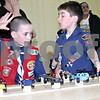 David Dulzo and Nickolai Glover, both of DeKalb, reach for their Pinewood Derby cars during a district competition held Sunday at the St. Mary Parish Memorial Hall in Sycamore.