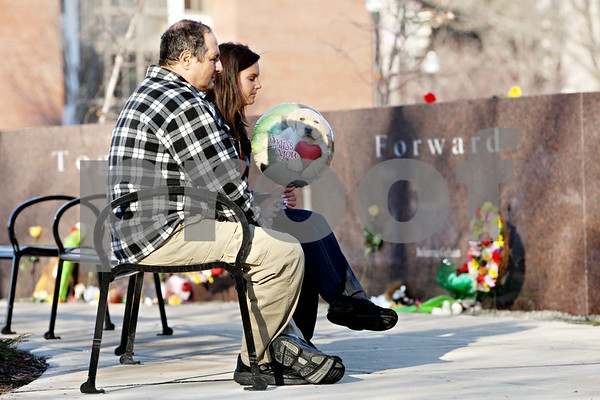 "Rob Winner – rwinner@daily-chronicle.com<br /> <br /> Greg Zanis (left), of Sugar Grove, and Ashley Cibulka, of Itasca, sit on a bench in front of Daniel Parmenter's engraved granite marker after ""NIU Remembers: A Day of Reflection,"" in DeKalb, Ill., on Monday, Feb. 14, 2011."