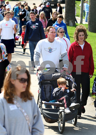 Kyle Bursaw – kbursaw@daily-chronicle.com<br /> <br /> Don Malcolm pushes three-year-old Anderson Malcolm in a stroller as he and other participants in the March for Babies walk away from Hopkins Park to start the march in DeKalb, Ill. on Saturday, April 30, 2011.