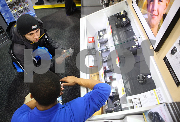 Kyle Bursaw – kbursaw@shawmedia.com<br /> <br /> Best Buy employee James McCarter (bottom) helps answer Brandon Wagner's questions about a camera lens on Friday, Nov. 25, 2011.