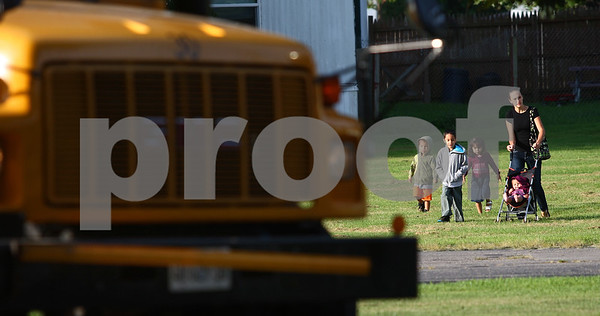 Kyle Bursaw – kbursaw@daily-chronicle.com<br /> <br /> Tiffany Wright walks with her children to the bus at Waterman Elementary where her son Enrique Rivera (second from left) will take a bus to Shabbona Elementary for the first day of school on Friday, Aug. 12, 2011.