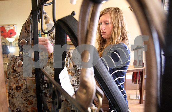 Kyle Bursaw – kbursaw@daily-chronicle.com<br /> <br /> Dani Emmert, hangs up purses for a display at Stomp Shoes in preparation for the annual Spring Fling sale in Sycamore, Ill. on on Saturday, March 19, 2011.