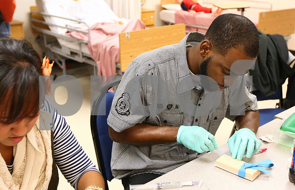 Kyle Bursaw – kbursaw@shawmedia.com<br /> <br /> Quincy Kimble gives an injection to his practice pad in his Maternal Health Nursing class at Kishwaukee College on Tuesday, Oct. 25, 2011. Kimble, 25, returned to school in the summer of 2009 after being laid off earlier that year. He is scheduled to complete his nursing degree in May 2012.