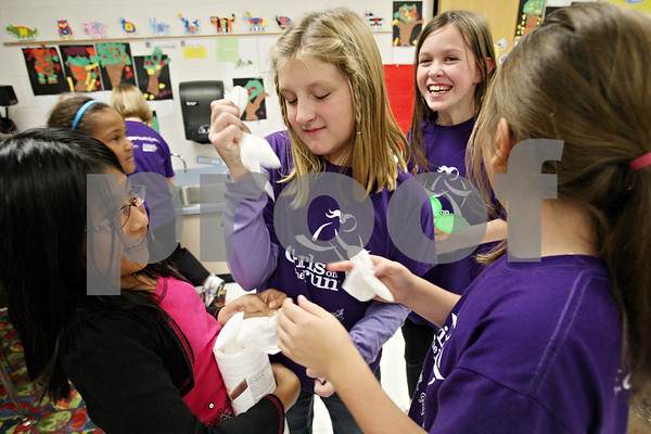 Rob Winner – rwinner@shawmedia.com<br /> <br /> Fifth grader Emma Bafia (center) grabs a disinfectant wipe while cleaning a kindergarten classroom at South Prairie Elementary School in Sycamore as part of a community service project for Girls on the Run on Tuesday. Girls on the Run is a national program designed to help boost self esteem and promote physical activity for girls in third through fifth grades.