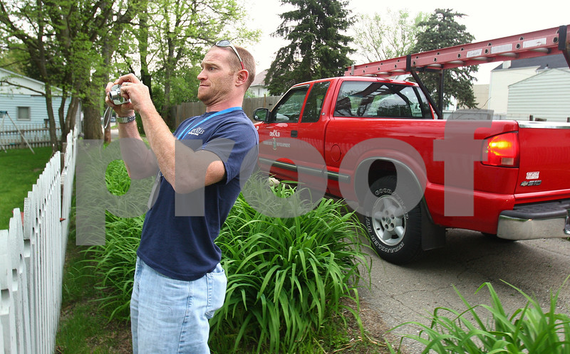 Kyle Bursaw – kbursaw@daily-chronicle.com<br /> <br /> Roger Votaw, a property maintenance inspector, photographs a property with code violations in DeKalb, Ill. on Friday, May 13, 2011.