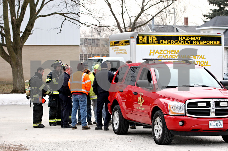 Rob Winner – rwinner@daily-chronicle.com<br /> <br /> Firefighters and hazmat technicians gather outside the 300 block of Eureka Street in Genoa after a hazardous material leak  on Wednesday afternoon.