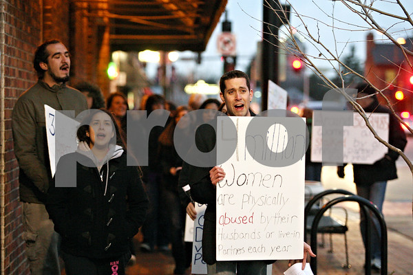 Rob Winner – rwinner@daily-chronicle.com<br /> <br /> Participants of Safe Passage's first Take Back the Night march, including Ulysses Diaz (from left to right), Alyssa Thomson, and Joe Hartsoe, walk east on Lincoln Highway in downtown DeKalb on Thursday evening.
