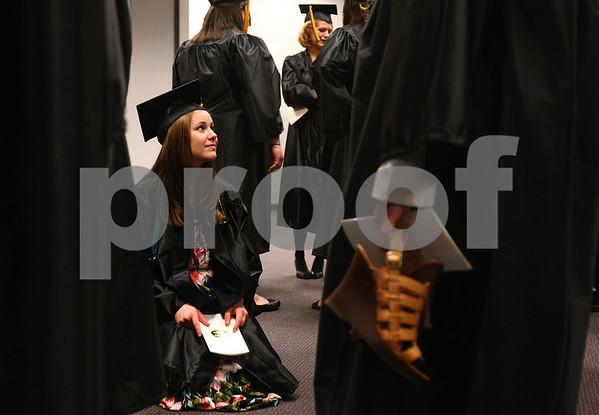Kyle Bursaw – kbursaw@daily-chronicle.com<br /> <br /> Kishwaukee College nursing student Lisa Leoni kneels amongst fellow graduates waiting in line prior to the graduation ceremony on Saturday, May 14, 2011.