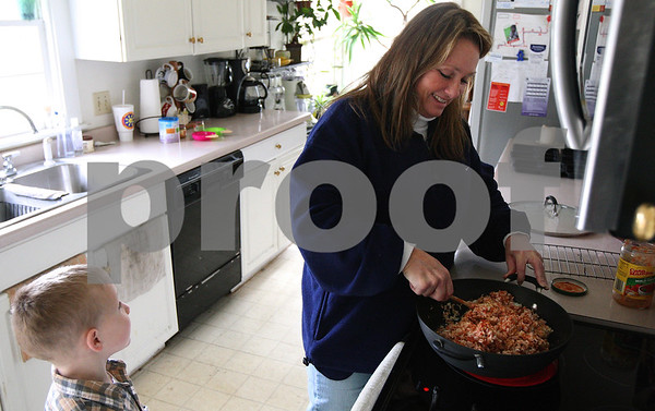 Kyle Bursaw – kbursaw@shawmedia.com<br /> <br /> Diana Hodge stirs up a mixture of brown rice, white rice, tuna and salsa for the children in her daycare at lunch time on Thursday, Dec. 8, 2011 while her son Mikey Hodge, 5, looks on. The lunch, which follows the guidelines set by the Child and Adult Care Food Program, also includes vegetables, fruit and milk.