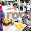 Rob Winner – rwinner@daily-chronicle.com<br /> <br /> While working at the Crump Family Gardens stand at the DeKalb Farmers Market on Thursday, Aug. 11, 2011, Megan Fort (from left to right), 16, accepts a voucher for jalapenos from DeKalb resident Guadalupe Parra while buying vegetables with her children Juan Martinez, 5, and Jonathan Martinez, 2.