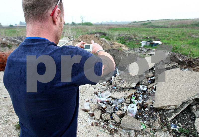 Kyle Bursaw – kbursaw@daily-chronicle.com<br /> <br /> Roger Votaw, a property maintenance inspector, photographs an empty lot in a subdivision where someone has dumped garbage in DeKalb, Ill. on Friday, May 13, 2011.