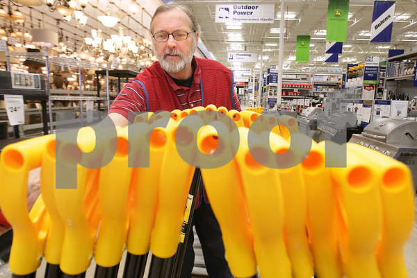Kyle Bursaw – kbursaw@daily-chronicle.com<br /> <br /> Jon Reisner, an outdoor sales specialist, puts up a display of ergonomic snow shovels at Lowe's Home Improvement in DeKalb, Ill. on Tuesday, Feb. 1, 2011.