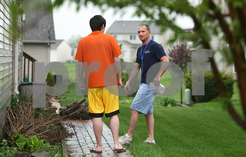 Kyle Bursaw – kbursaw@daily-chronicle.com<br /> <br /> Roger Votaw (right), a property maintenance inspector, speaks with a DeKalb resident about the brush (lower left) against the side of the building that violates city code on Friday, May 13, 2011.